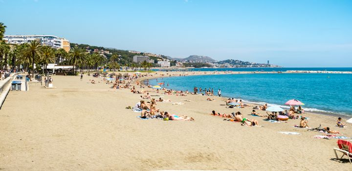 Malaga, Spain - May 26, 2018. Holidaymakers sunbathing on Malagueta beach, Malaga, Costa del Sol, Malaga Province, Andalucia, Spain, Western Europe