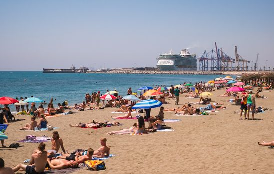 Malaga, Spain - June 26, 2018. People on the Malagueta beach with Royal Caribbean Independence of the Seas in the background, Costa del Sol, Malaga Province, Andalucia, Spain
