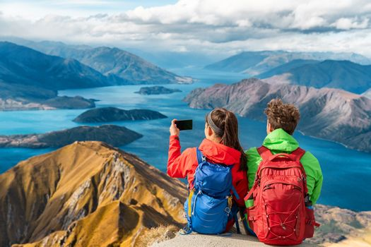 Hikers looking at view on mountain top summit on hiking travel vacation - couple taking photo with phone. Wanderlust adventure people relaxing. Summit of famous hike to Roys Peak, New Zealand.
