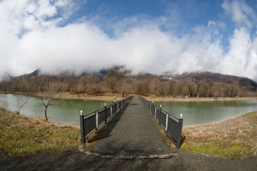 Forest lake with bridge during the sunny day with winter trees and blue cloudy sky. Beautiful natural mountain lake with forest in the background and stormy clouds on the sky. Azerbaijan nature