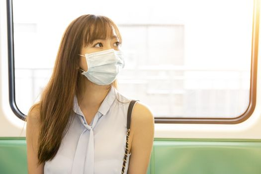 business woman wearing face mask and sitting in subway train