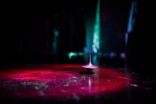 Totem spinning top spinning, wobbling and stopping. Spinning top on mirror surface with toned smoke background light. Whirligig in action in dark room on table. Selective focus