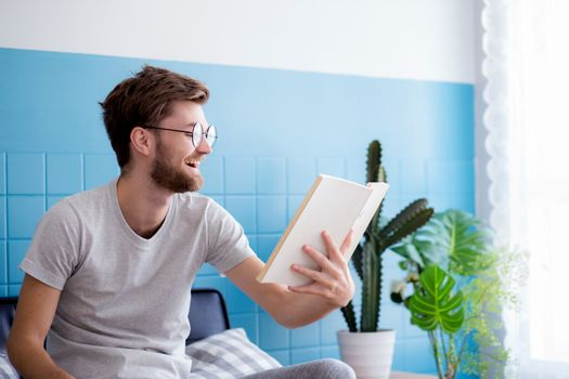 Young man wear glasses reading book on sofa with enjoy and laugh