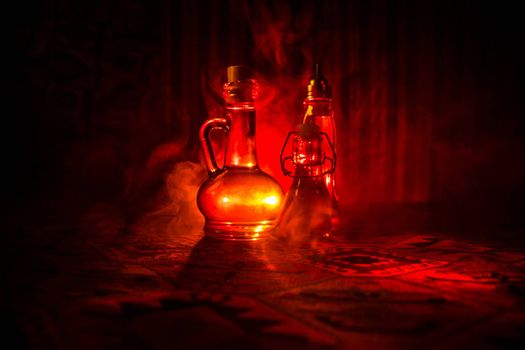 Antique and vintage glass bottles on dark foggy background with light. Poison or magic liquid concept.