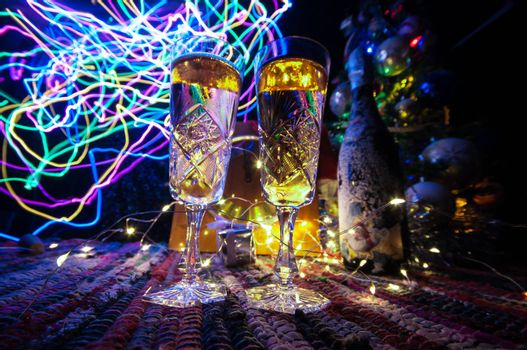 Two glasses of champagne with Christmas decoration. Traditional winter holiday alcohol drink in snow with creative New Year artwork. Copy space. Selective focus