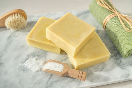Natural soap homemade bars for exfoliation skincare with epsom salts and ramie towel scrubbing brush on marble top