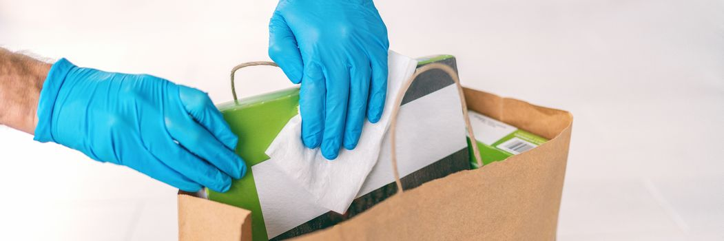 Coronavirus wiping down grocery packages after receiving home delivery wearing gloves, using disinfecting sanitizing wipes to wipe the surfaces clean. Cleaning of COVID-19 virus.