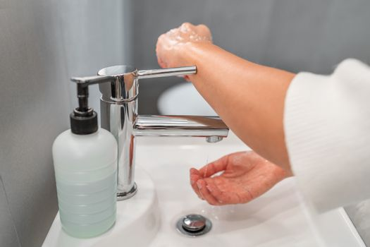 Washing hands hygiene step closing faucet tap with arm instead of hand after drying hands for COVID-19 contamination prevention. Precaution in bathroom