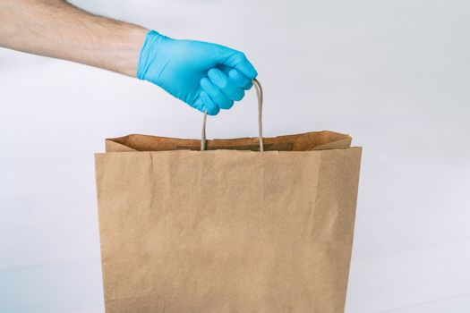 Home delivery during COVID-19 quarantine from coronavirus self isolation lockdown. Grocery store shopping delivery man giving paper bag wearing blue glove as protection for Corona virus prevention