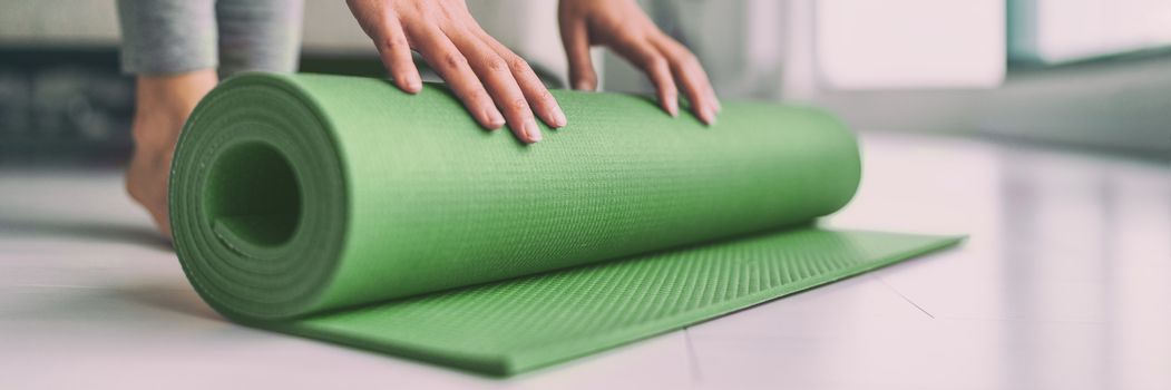 Home meditation woman rolling yoga exercise mat in living room for pilates workout online class banner panoramic apartment lifestyle.