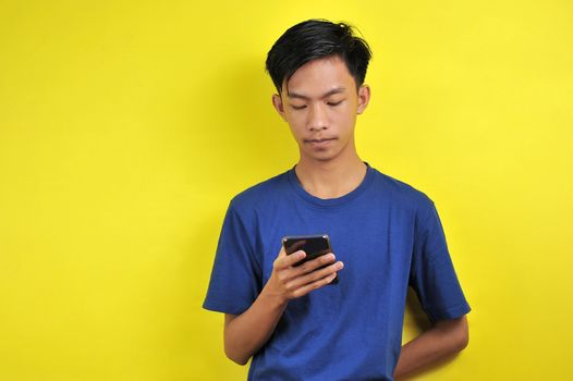 Portrait of serious Asian man using smartphone isolated on yellow background