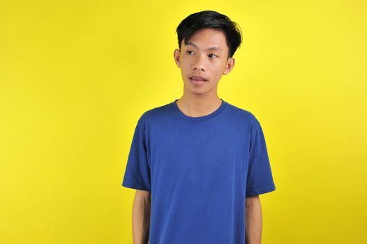 Portrait of happy young Asian man looking at the copy space, isolated on yellow