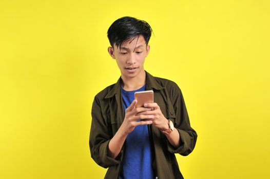 Shocked face of Asian man in white shirt looking at phone screen, isolated on yellow background.