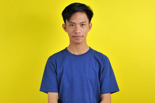 Portrait of young Asian man with confident smiling, isolated on  yellow