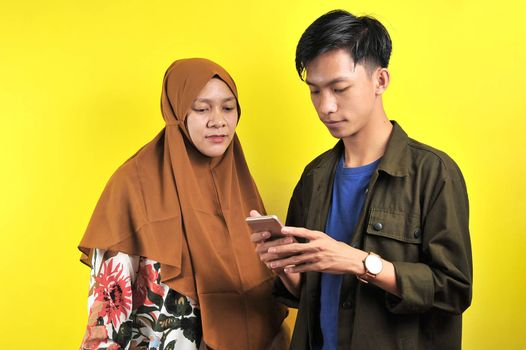 Portrait of two people look at smartphone display, isolated on yellow background