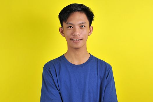 Portrait of happy young Asian man smiling in front of the camera, isolated on yellow