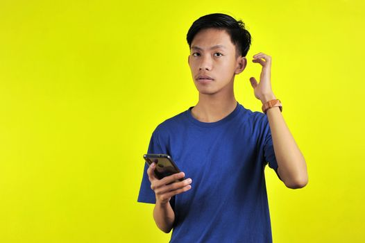 Portrait of confused man looking at smartphone, isolated on yellow background