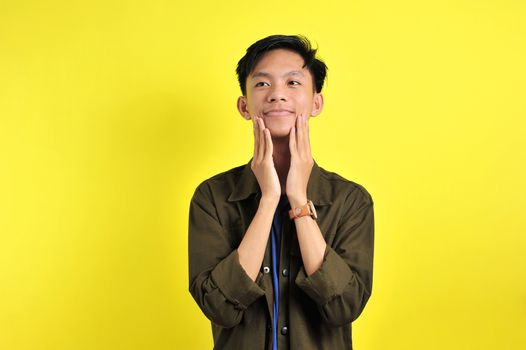 Happy of young Asian man smiling confident look at on top, isolated on yellow background