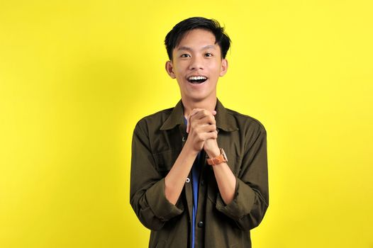 Portrait of happy Young Asian man surprised and shocked, isolated on yellow