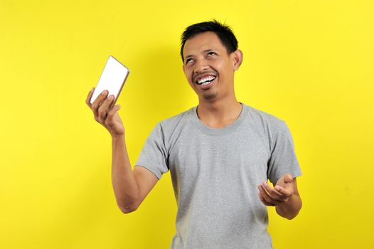 Funny Young Asian man holding smartphone, isolated on yellow background