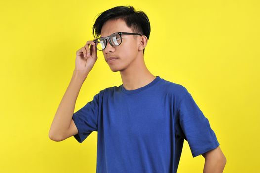Portrait of gentle Asian man wearing glasses, isolated on yellow background