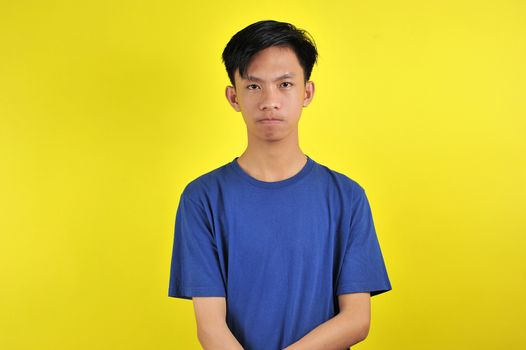Portrait of young Asian man close mouth gesture, isolated on  yellow
