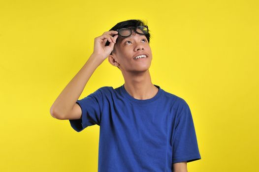 Happy Young Asian man smiling wearing glasses look at copy space, isolated on yellow background