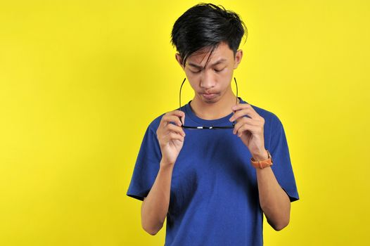 Feeling bored, Young Asian man wearing glasses, isolated on yellow background