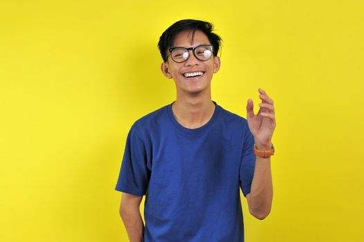 Happy Young Asian man smiling wearing glasses, isolated on yellow background