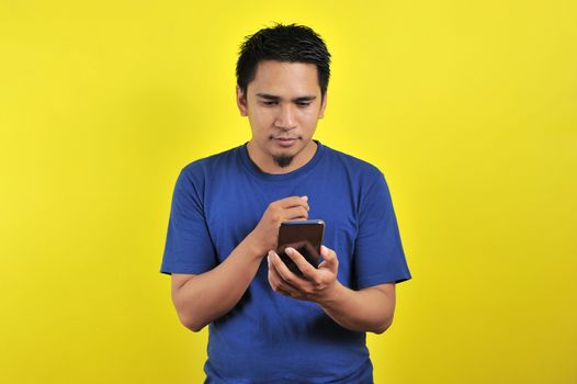 STRAIGHT FACE of Asian man in white shirt looking at phone screen on yellow background.