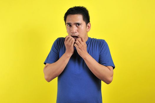 Handsome young man looking afraid, stressed and nervous with hands on mouth biting nails, over yellow background