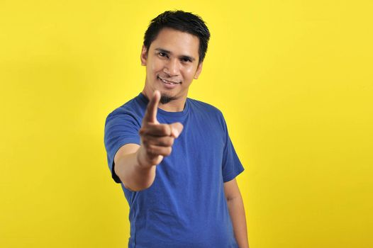 Happy young Asian man smiling pointing to the camera, isolated on yellow