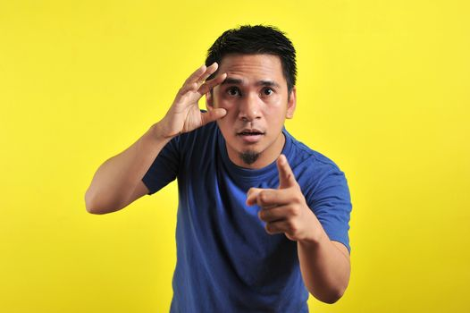 Young Asian man open his eyes and pointing the camera, isolated on yellow background