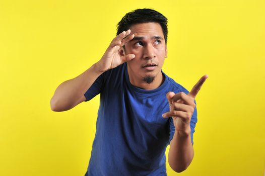 Young Asian man open his eyes and pointing the blank area, isolated on yellow background