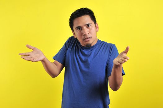 Young man asking questions with hands raised, isolated on yellow background