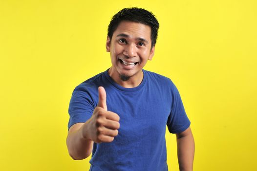 Portrait of young Asian man laughing with showing thumbs up at camera, isolated on yellow