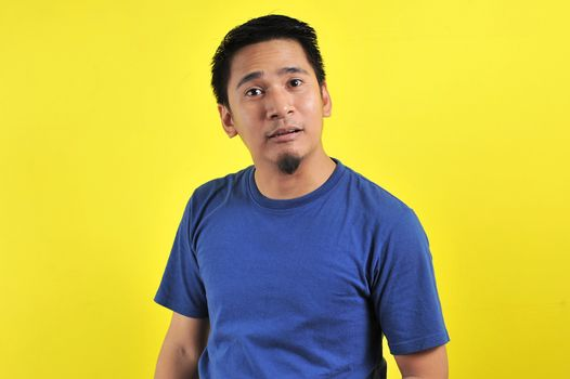 Young Asian man doing funny mouth gesture, isolated on yellow background