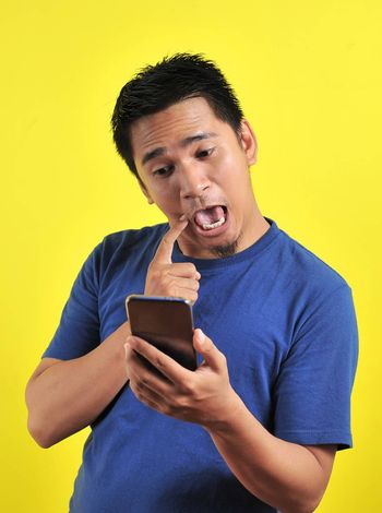 Funny Asian man using cellphone, isolated on yellow background