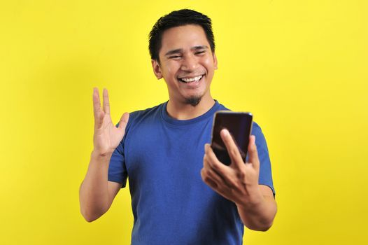 Happy young good looking Asian man smiling using cellphone, isolated on yellow background