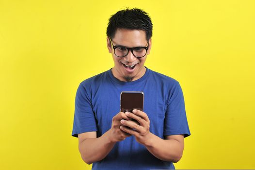 Shocked face of Asian man in blue shirt looking at phone screen on yellow background.