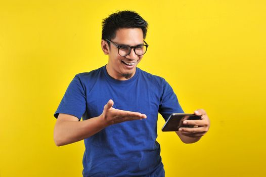 Happy excited Asian man looking at his smartphone and raising his arm up to celebrate success or achievement, isolated on yellow