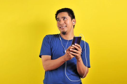 Asian man in casual blue t-shirt wearing headset listening to music from smartphone looking at the copy space, on yellow background.
