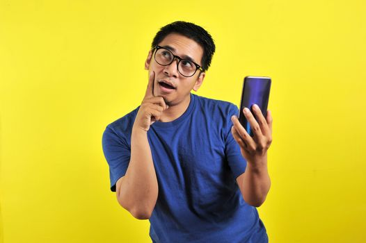 Asian man holding smartphone doing thinking gesture, isolated on yellow background