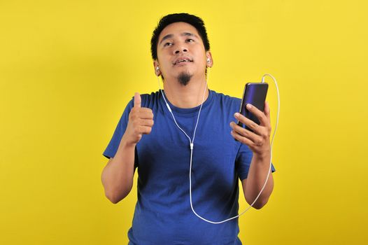 Asian man in casual blue t-shirt wearing headset listening to music from smartphone, isolated on yellow background.