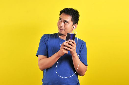 Asian man listening of music from smartphone looking at copy space, isolated on yellow background