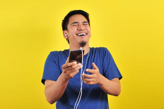 Portrait of excited Asian man laugh happily listening of music from smartphone, isolated on yellow background