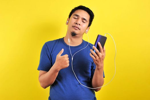 Portrait of Asian man listening of music from smartphone with closed eyes, isolated on yellow background