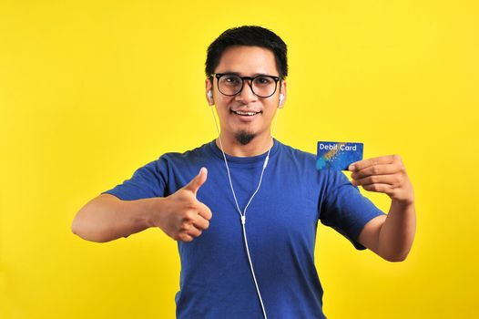 Young Asian man love his debit card, isolated on yellow background