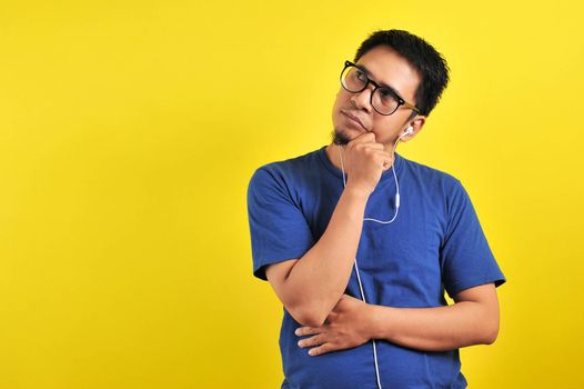 Man wear glasses, wondering or imagining ideas, daydreaming and looking up to copy space against orange wall