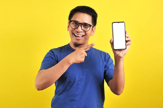 Happy Asian man showing a phone screen and pointing, isolated on yellow background